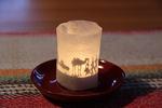 Tuikkukynttilän valo heijastaa seimihahmojen varjokuvat paperille