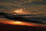 Viimeisten säteitten värjätessä kallioon saapuvat aallot hehkuvan laavan värisiksi