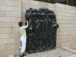 Juutalaisilla on tapana laittaa pieniä kiviä vainajiensa haudoille. Tässä Kaija laittaa kiveä Janusz Korczakin muistomerkille